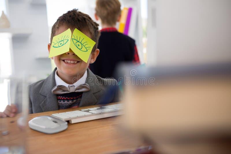 男孩当与稠粘的笔记的商业主管关于他的眼睛 免版税库存图片