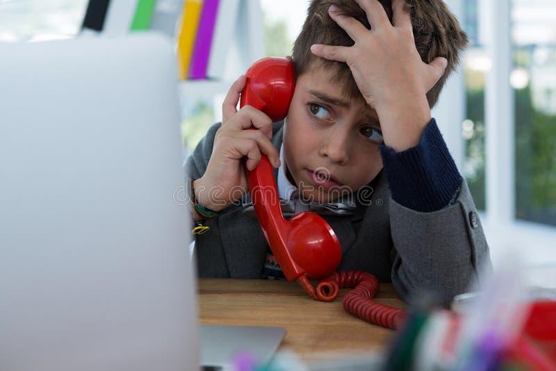 男孩当商业主管谈话在电话 免版税库存照片