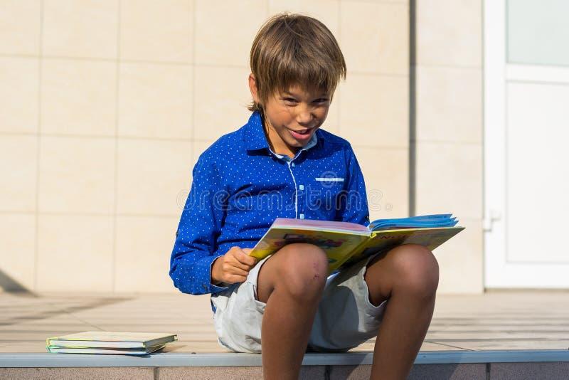 男孩恶霸坐在学校前面的步并且读 免版税库存照片