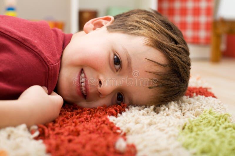 男孩愉快的放置的地毯 库存图片