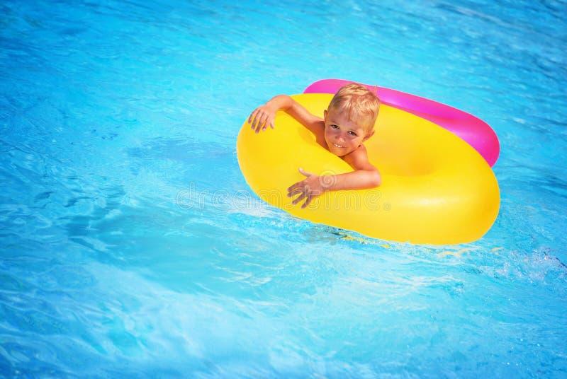 男孩愉快的池游泳 免版税库存图片