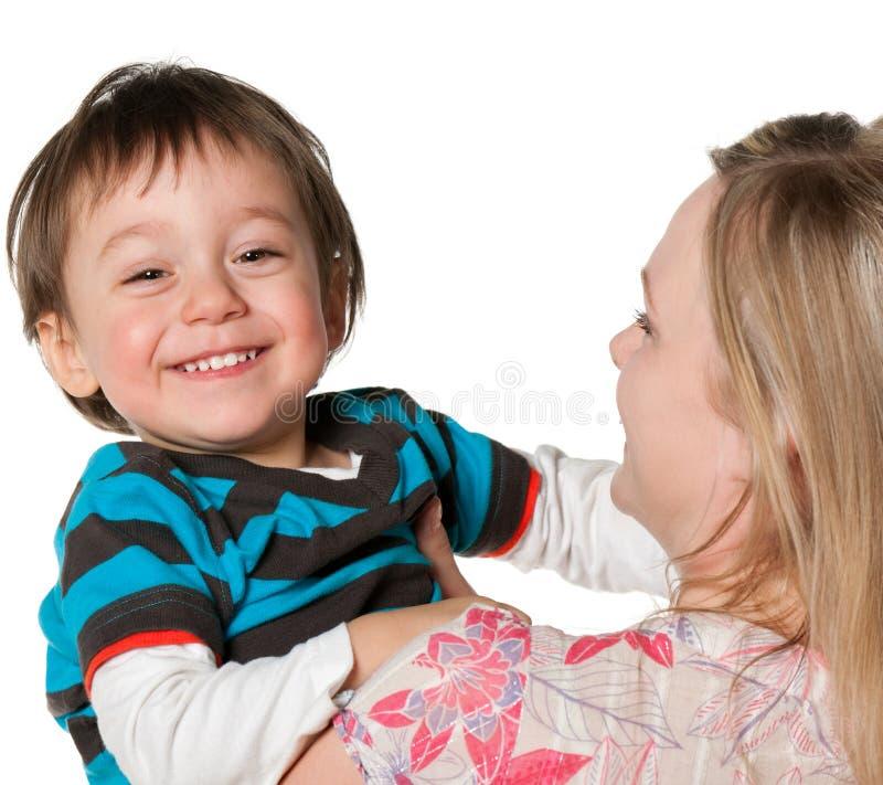 男孩愉快的藏品一点母亲微笑 免版税库存照片