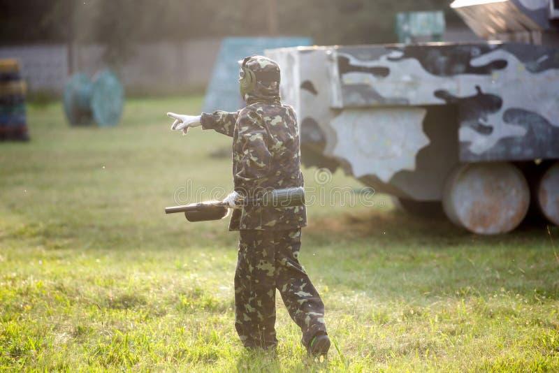 男孩打在领域的迷彩漆弹运动 迷彩漆弹运动球员两个队以与面具,盔甲,在领域的枪的伪装形式 库存图片