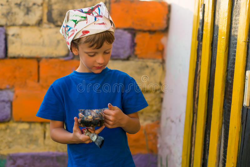 男孩执行绘画工作油漆户外夏天 库存照片