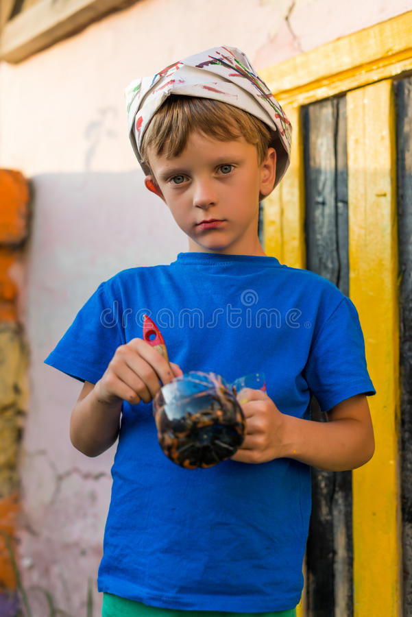 男孩执行绘画工作油漆户外夏天 库存图片