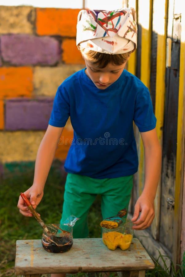 男孩执行绘画工作油漆户外夏天 免版税库存图片