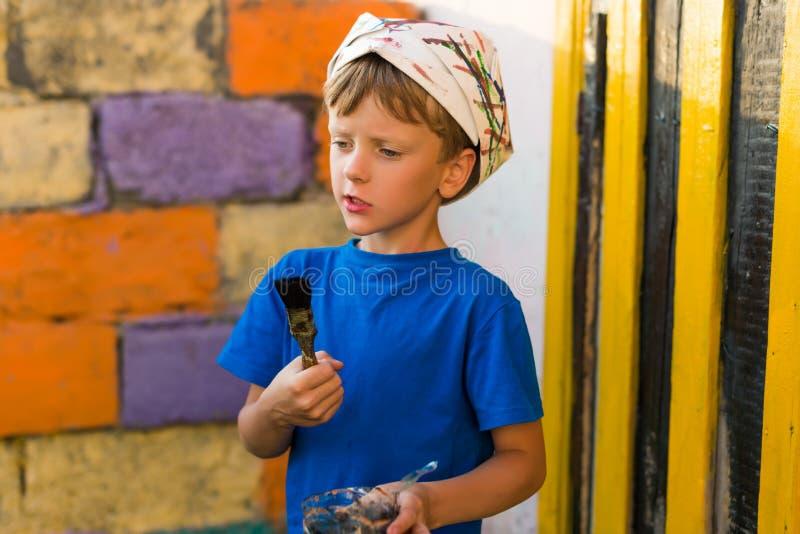 男孩执行绘画工作油漆户外夏天 免版税库存照片
