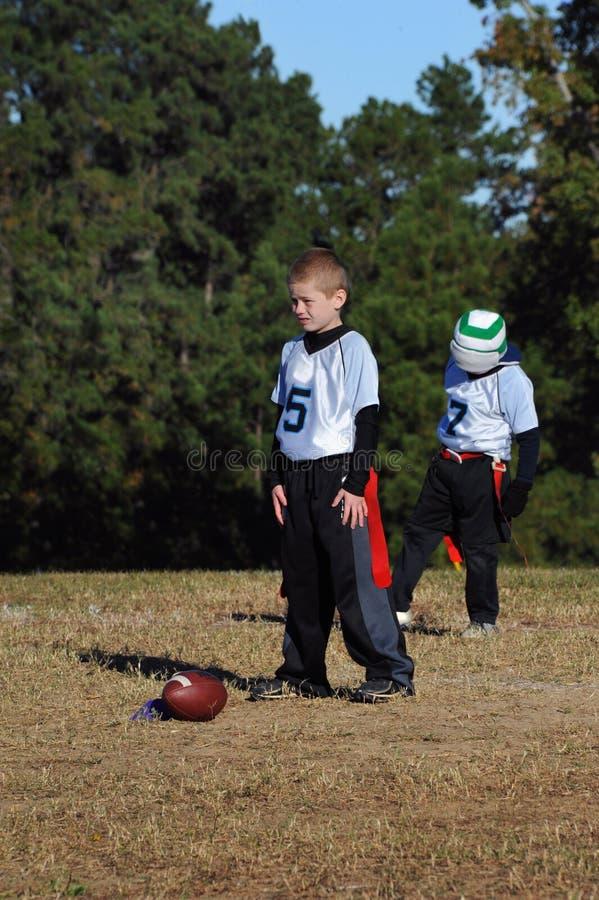 男孩扮演旗子的Flootball四分卫 库存图片