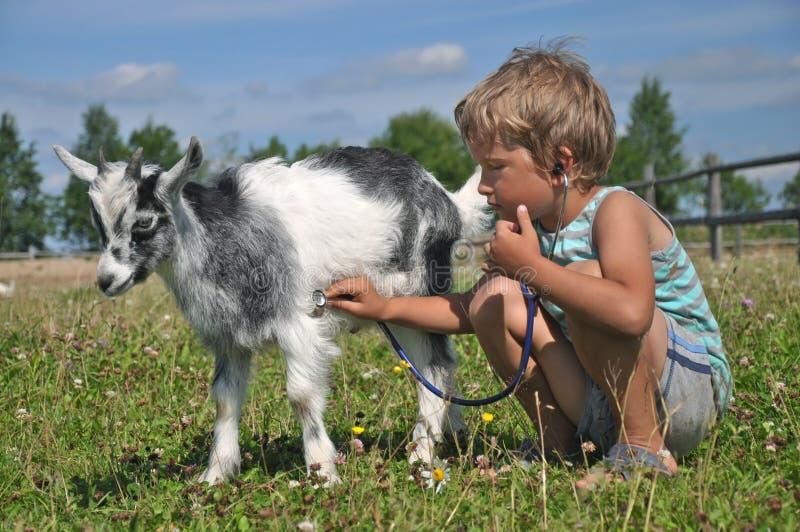 男孩扮演有山羊的一位狩医 免版税库存照片