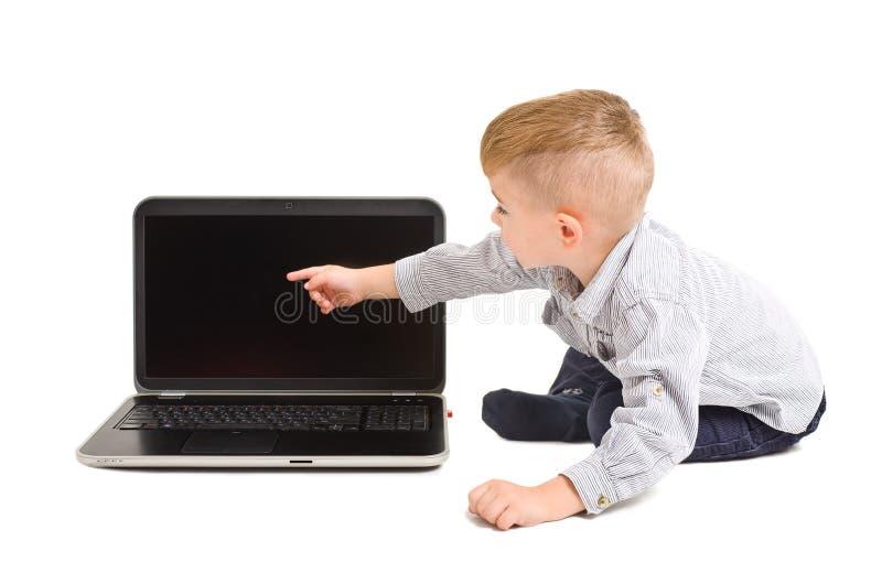 男孩把手指指向膝上型计算机屏幕  免版税库存图片
