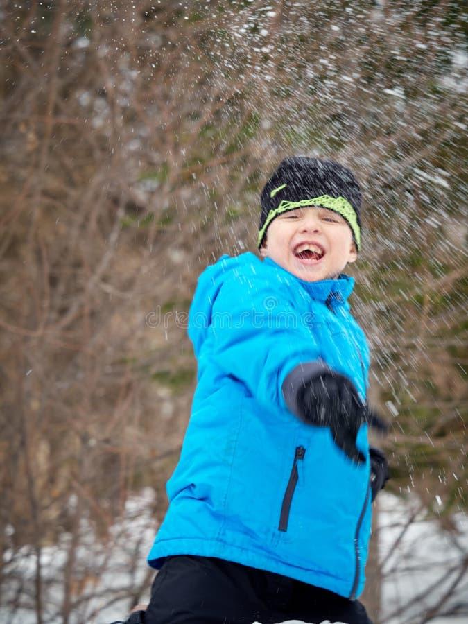 男孩投掷雪球 免版税图库摄影