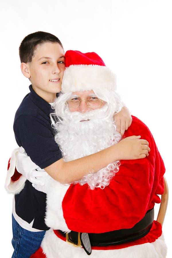 男孩拥抱的圣诞老人 图库摄影
