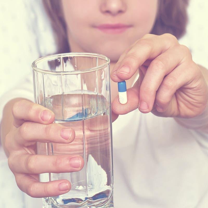 年轻男孩拿着一杯水,在背景 集中于一杯水和药片 库存照片