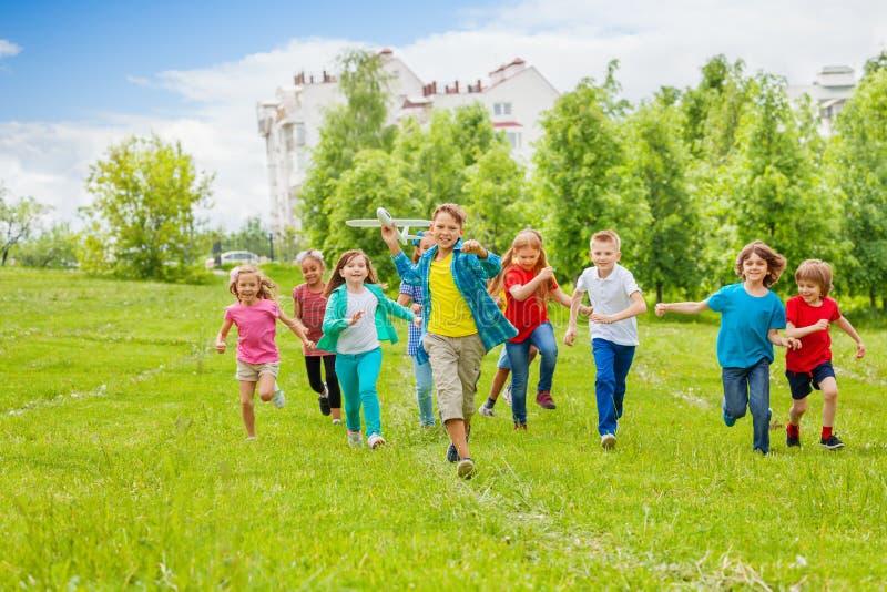 男孩拿着大白色飞机玩具和孩子后边 免版税库存图片