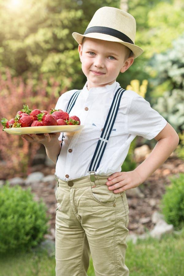男孩拿着成熟芳香草莓板材  免版税库存照片