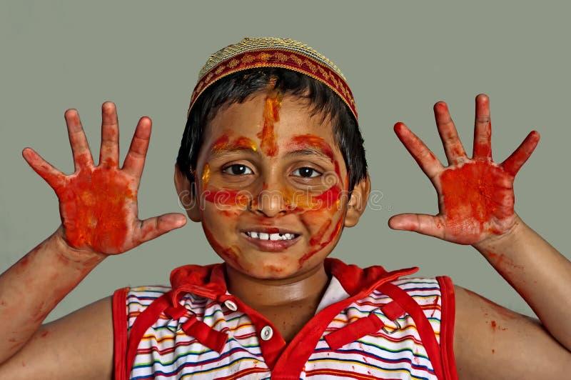 男孩接近的颜色面对微笑年轻人的holi 图库摄影