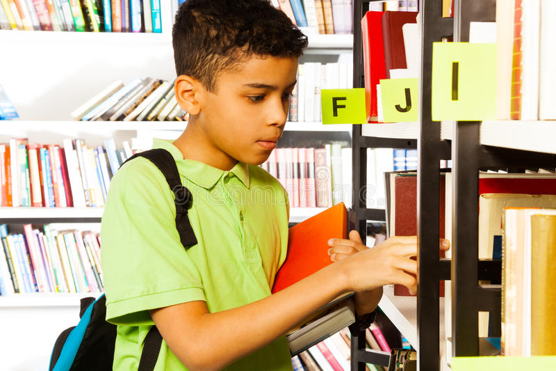 男孩搜寻在图书馆书架的书 免版税库存图片