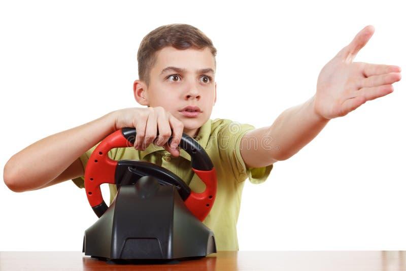 男孩播放一个驾驶的比赛控制台,隔绝在白色 图库摄影