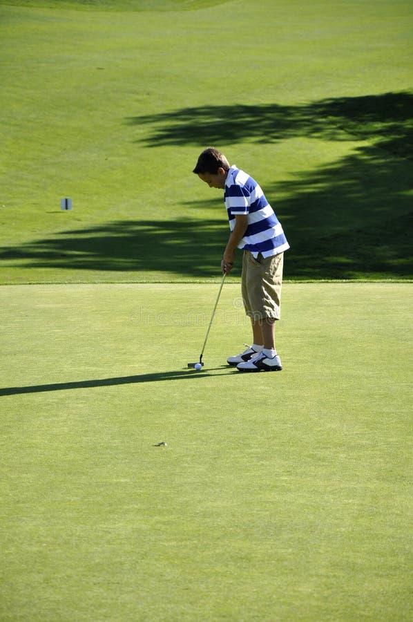 男孩放置年轻人的路线高尔夫球 库存照片