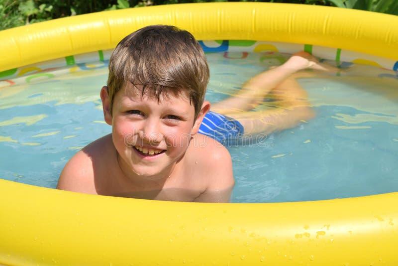 男孩是在一个可膨胀的水池 免版税库存图片