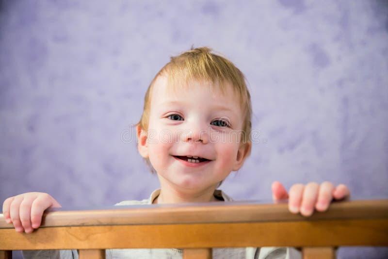 男孩是在小儿床 库存图片