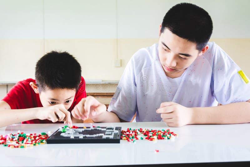 男孩是集中和焦点在演奏lego 图库摄影