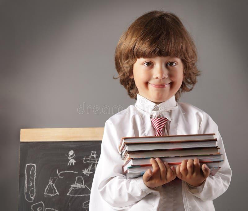 男孩有书的小学学生 免版税库存图片