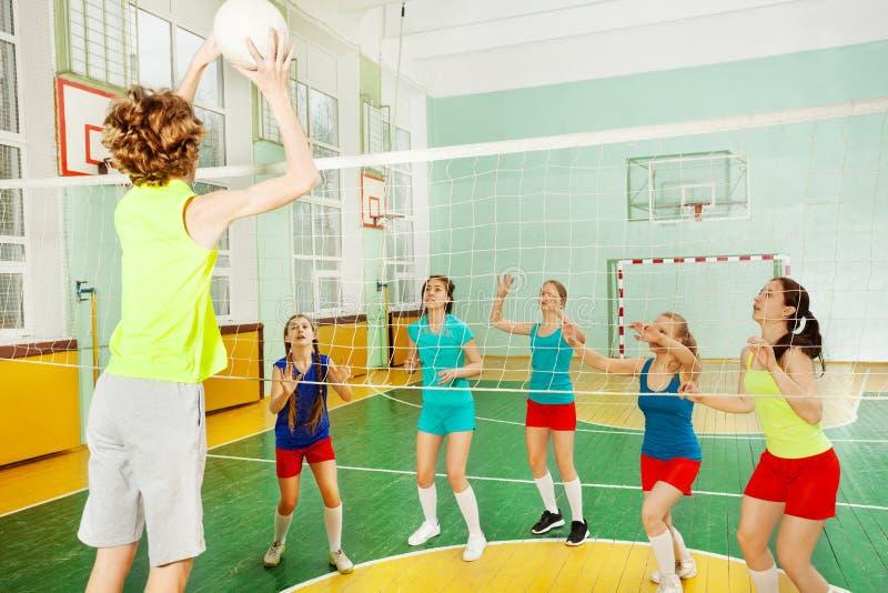 男孩服务在排球比赛期间的跃迁浮游物 免版税库存照片