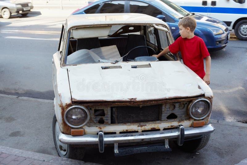 男孩检查生锈与残破的挡风玻璃汽车 免版税库存照片