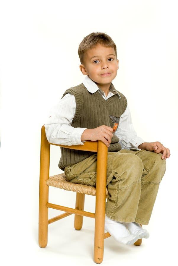 男孩椅子坐的年轻人 免版税图库摄影