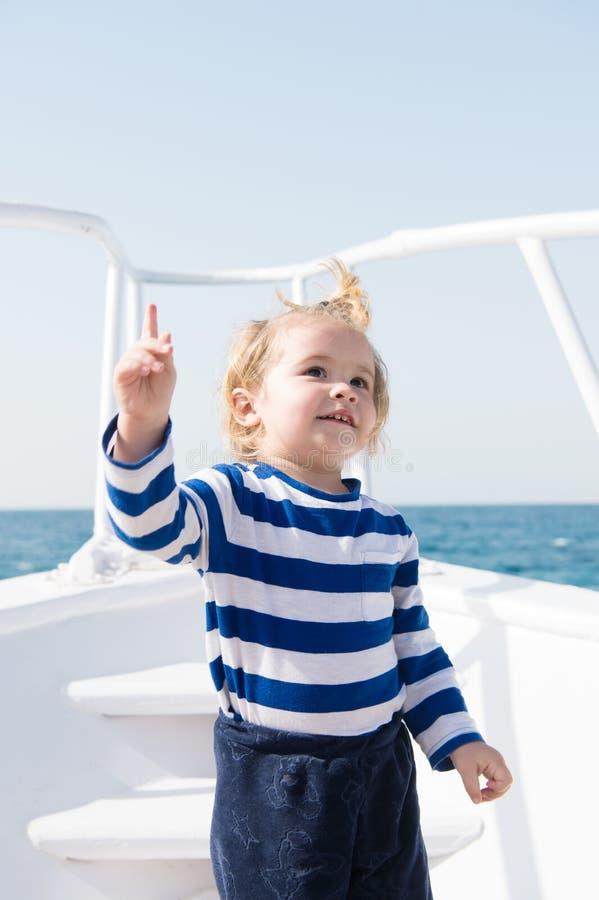 男孩概念 水手男孩 在船的男孩旅行在海 小男孩保持尖手指被举 在那查找 免版税库存照片
