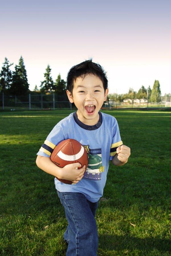 男孩橄榄球 库存图片