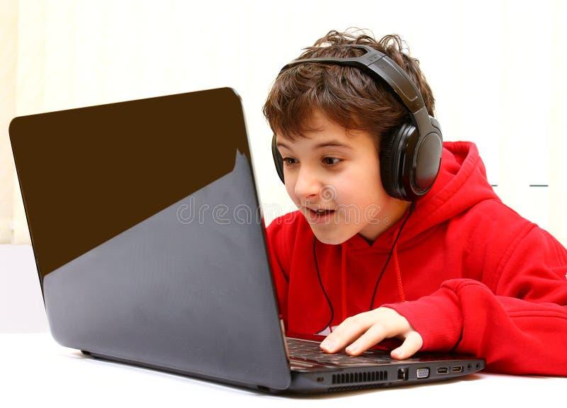 男孩比赛愉快膝上型计算机使用 库存照片
