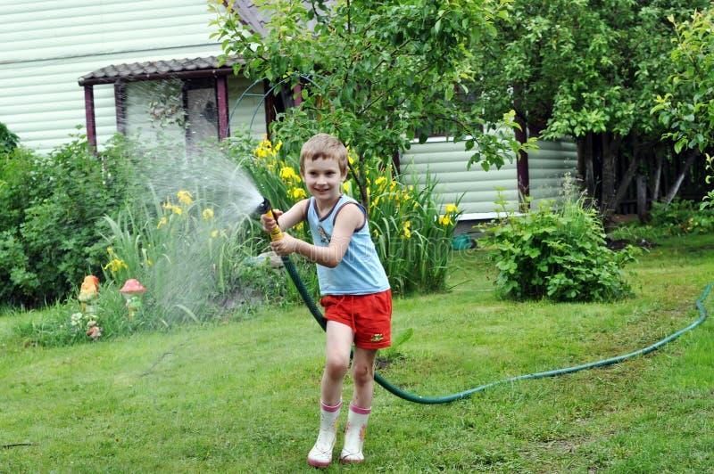 男孩水管草坪浇灌 免版税库存照片