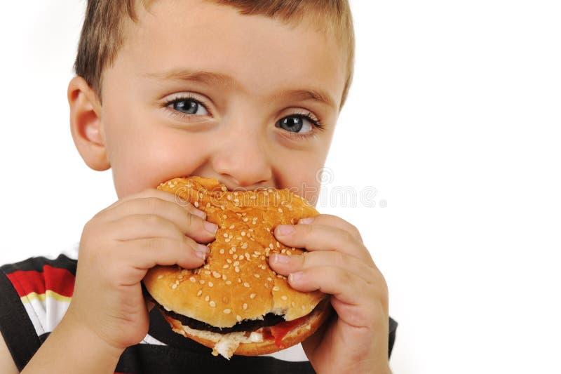 男孩汉堡吃 免版税库存图片