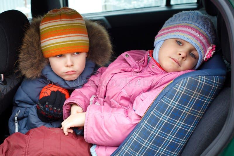 男孩汽车给女孩哀伤的冬天穿衣 免版税库存图片