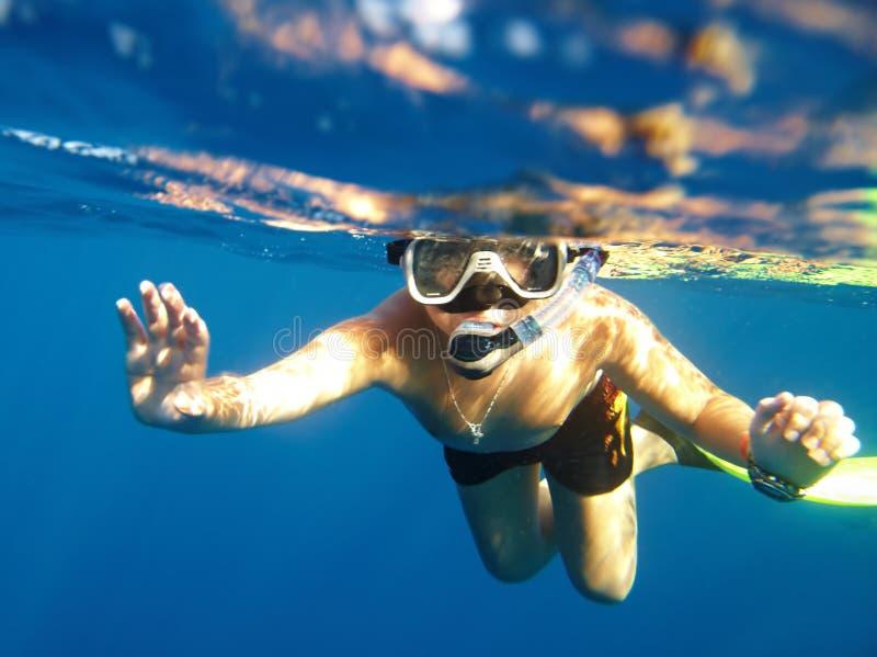 男孩浮动在水之下 免版税库存照片