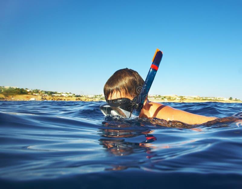 男孩浮动海运在水之下 库存图片
