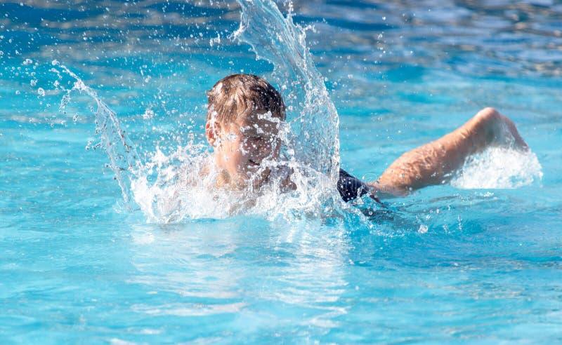 男孩游泳与飞溅在水公园 图库摄影