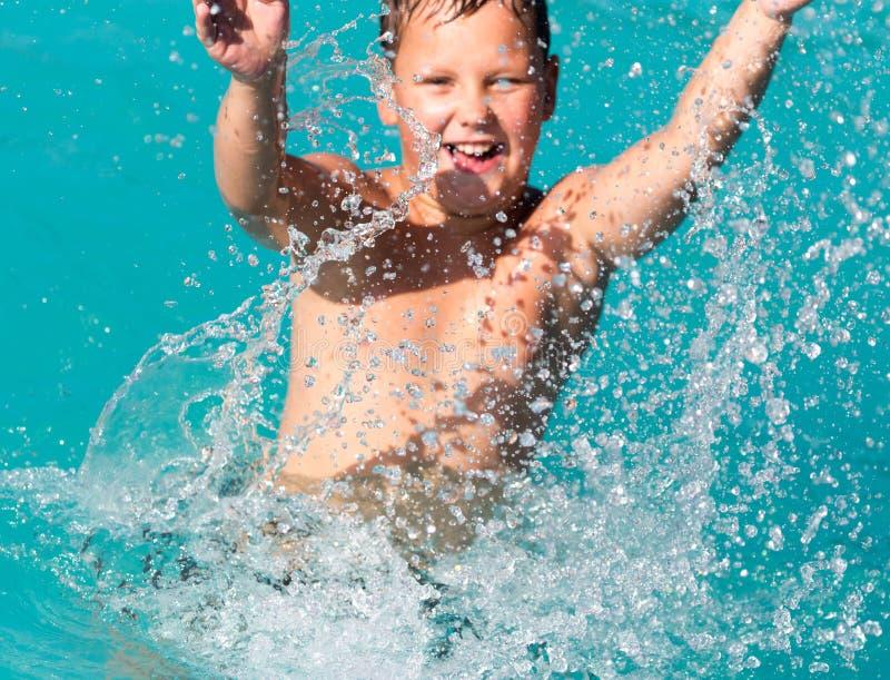 男孩游泳与飞溅在水公园 免版税库存照片
