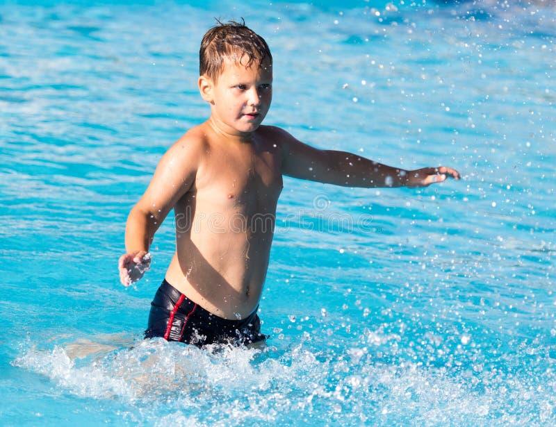 男孩游泳与飞溅在水公园 库存图片