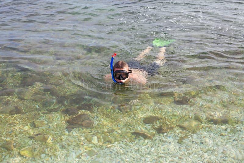 男孩游泳在面具的海和飞翅 库存图片