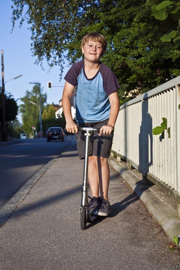 男孩滑行车街道 库存照片