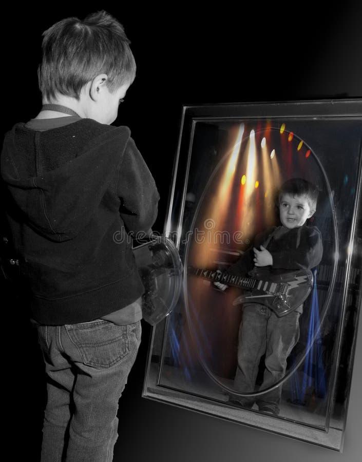 男孩演奏年轻人的吉他镜子 库存照片