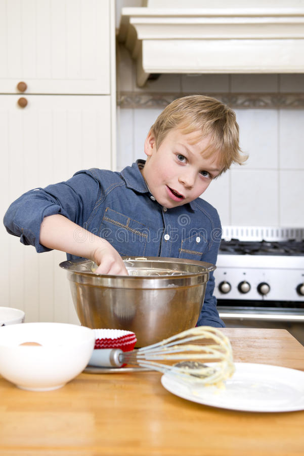 年轻男孩烘烤饼在厨房里 免版税库存图片