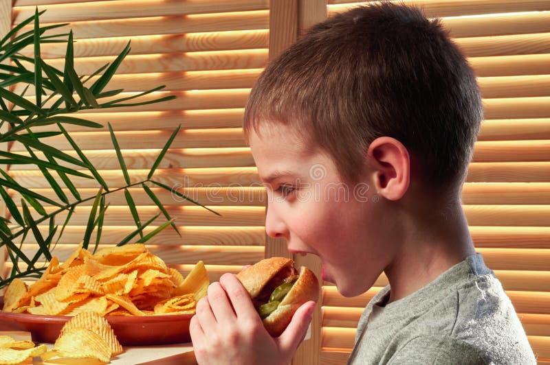 男孩热切地咬住可口大热狗 吃在咖啡馆的孩子食物 快餐 侧视图 免版税库存照片