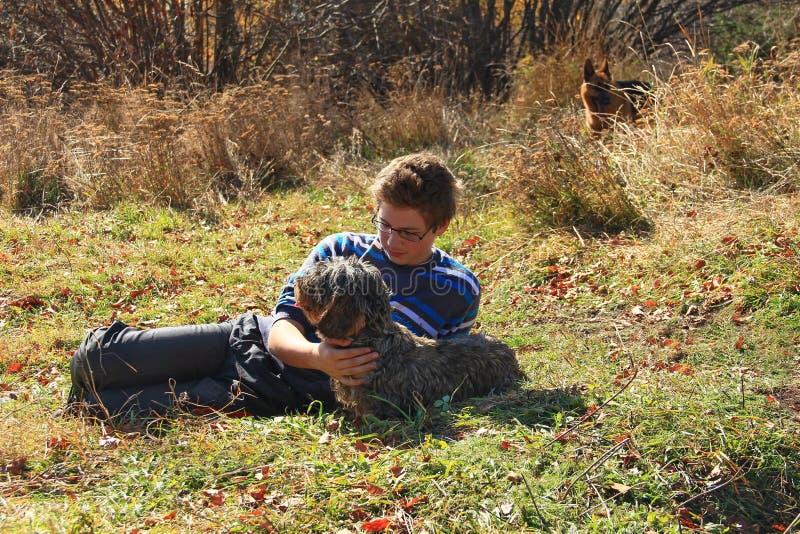 男孩爱抚达克斯猎犬狗 图库摄影
