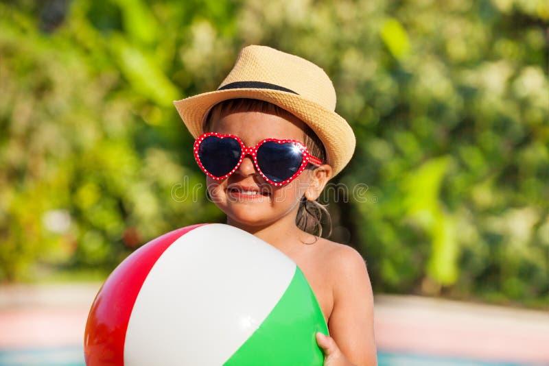 男孩特写镜头拿着球的帽子和太阳镜的 免版税图库摄影