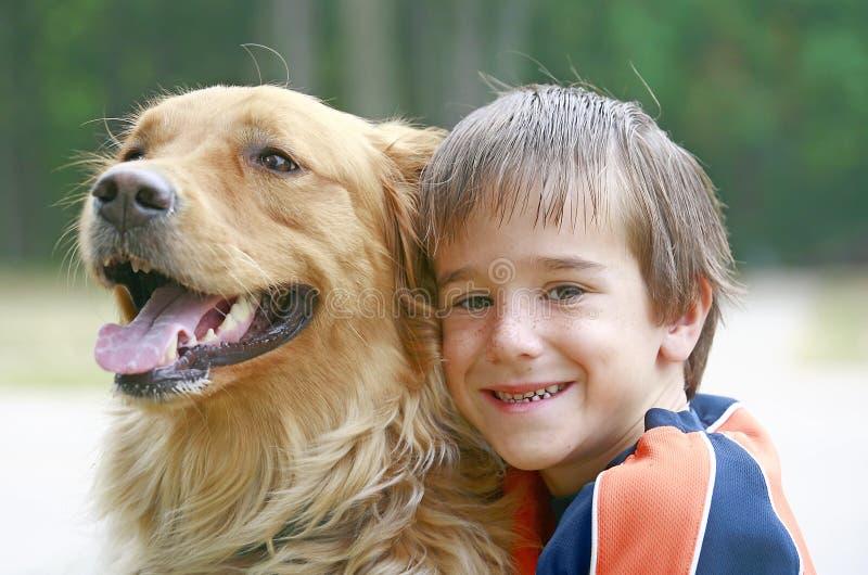 男孩狗拥抱 免版税图库摄影