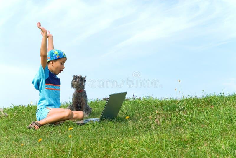 男孩狗膝上型计算机 库存图片